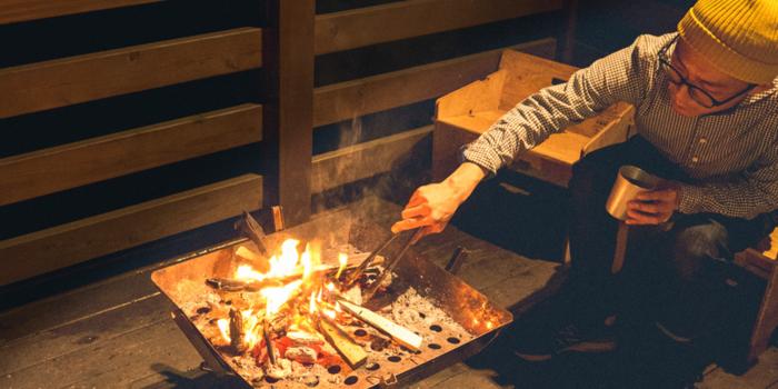 ベランダでYOKAのチェアに座り焚き火をする男性