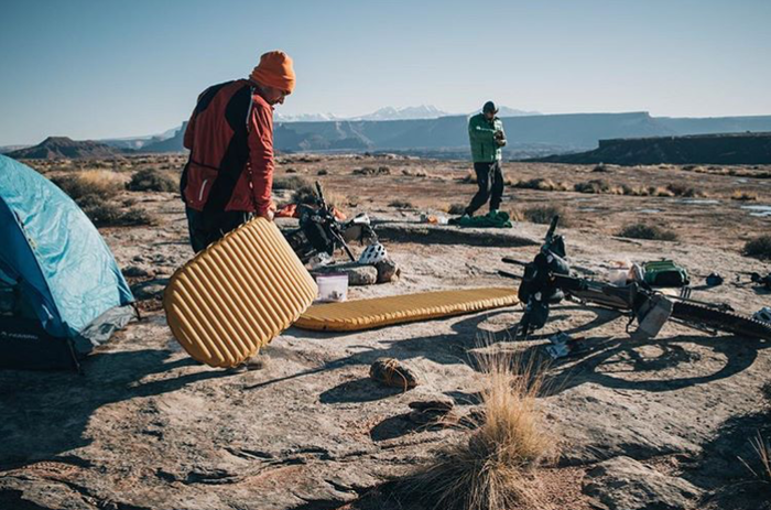 荒野でキャンプマットを運ぶ男性