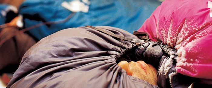 シュラフで口元以外くるまって寝る男性