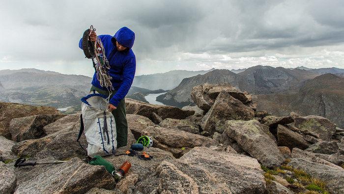 岩山の頂上でパタゴニアのリュックから荷物を取り出す人