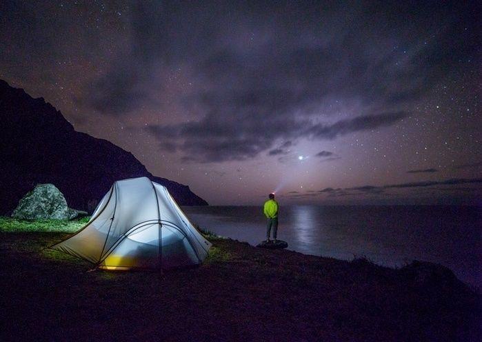 湖のすぐそばでソロキャンプをする男性と満天の星