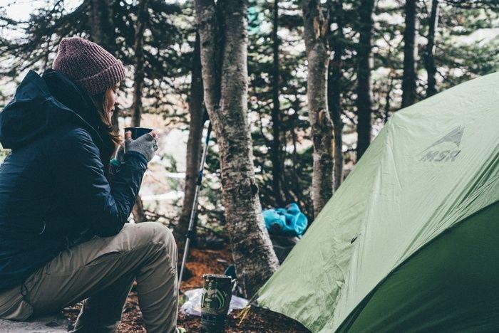 木々に囲まれたテントの側でカップを持つ女性