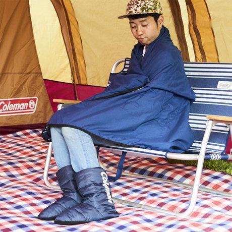 テントの中でアウトドアスリッパを履き、暖まる人