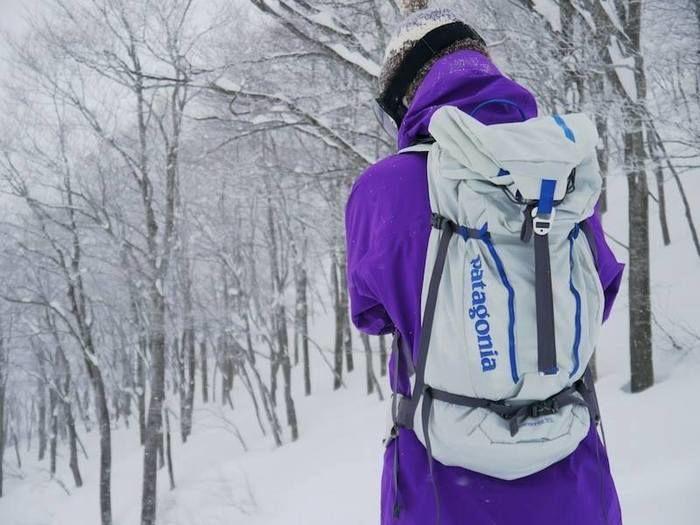 雪道でパタゴニアを背負っている人