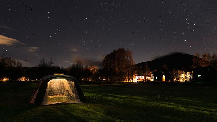 夜のキャンプ場でコタツで暖まる人々