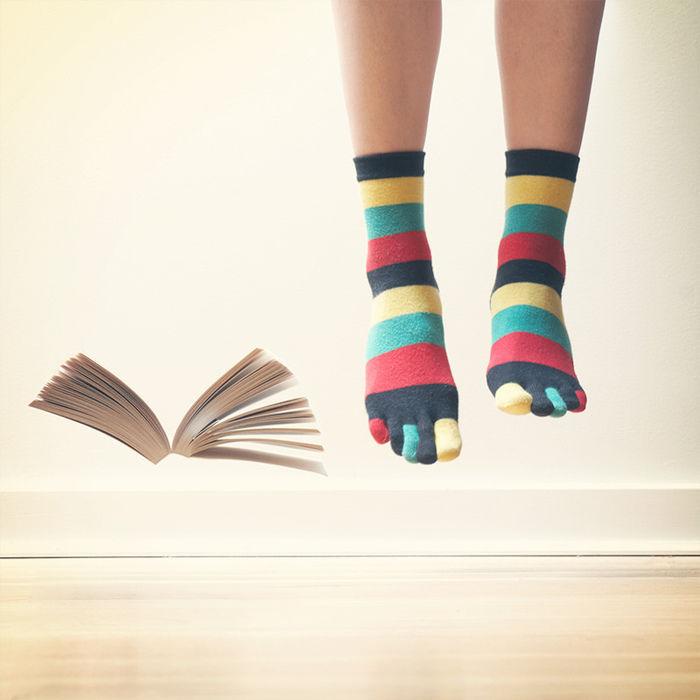 カラフルなレインボーの5本指ソックスをはいた足元と広がった本