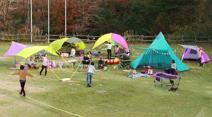 カラフルなテントを貼ってキャンプを楽しむ人々