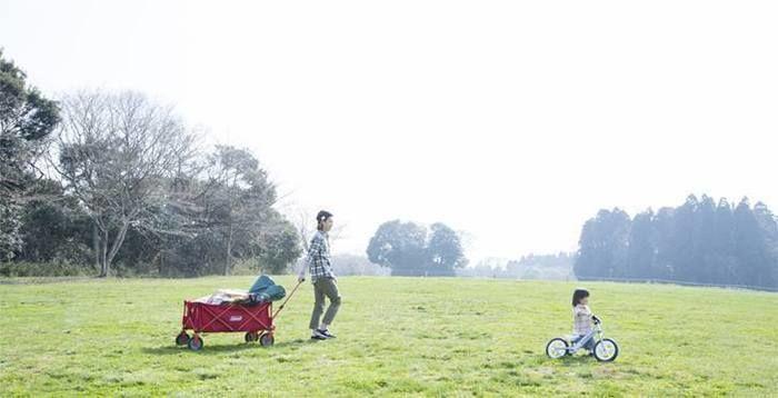 自転車に乗る女の子と荷物を引いてそのあとについていく親