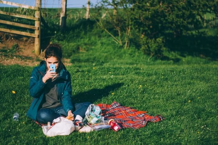 ピクニックの最中に携帯で写真をとる女性