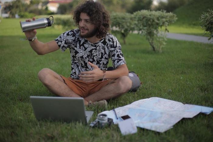 ピクニックにステンレスボトルを持ち出す男性