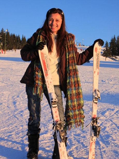 スキー板を持って笑う女性