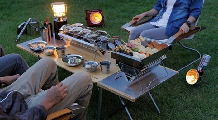ユニフレームの焚き火テーブルを設置して野外で食事を楽しむ様子