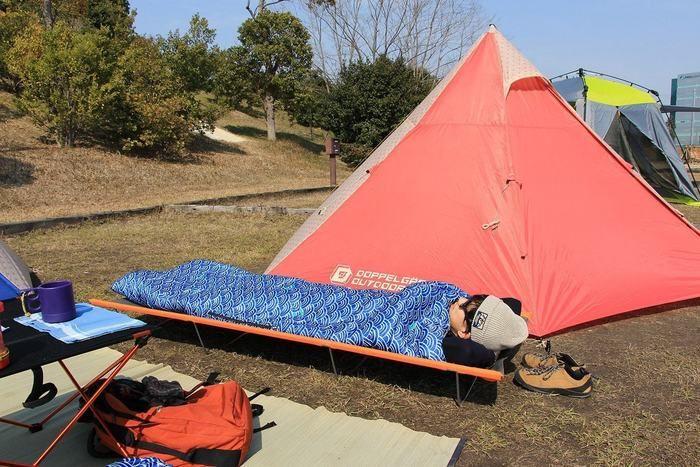 テントの横に置かれたコットで寝る男性