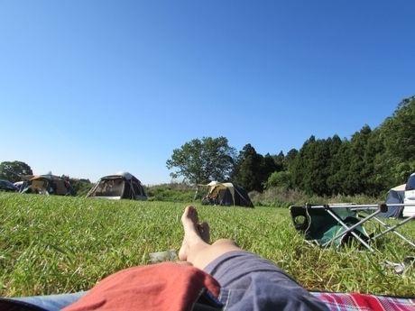 寝転がる男性の足元とキャンプ場