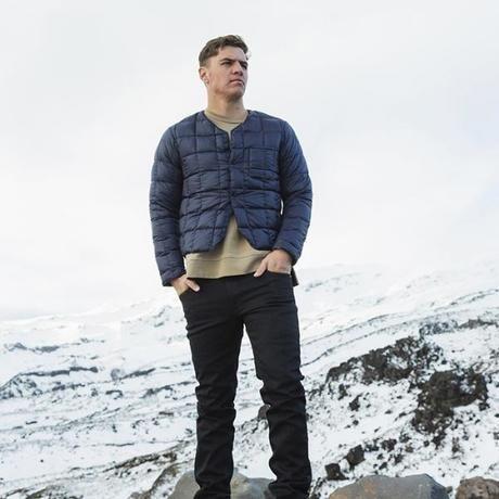 何がのダウンを着て雪山に立つ男性
