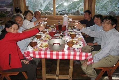 山小屋で大人数で食事をする様子