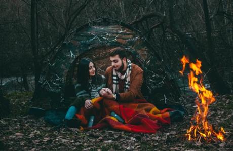 焚き火に温まり手をにぎり合う男女