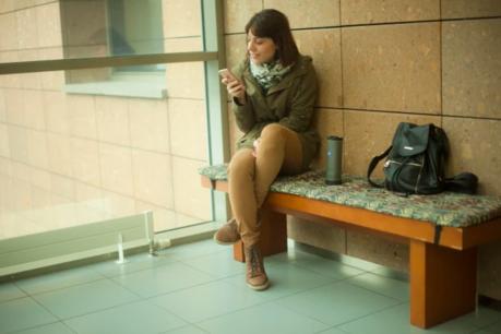 ベンチに座りYecup365で携帯を充電する女性