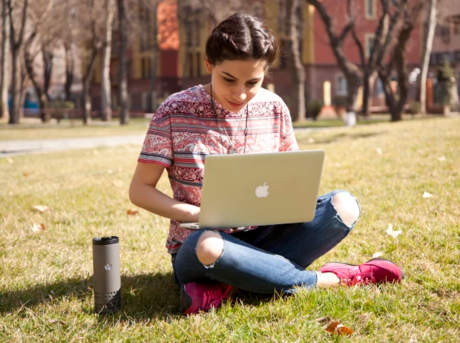 タンブラー横にパソコンで作業をする女性