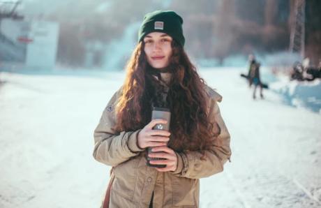 雪山でタンブラーを持った女性