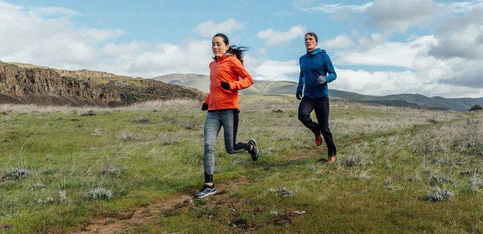 メレルのシューズをはいて山道を走る男女