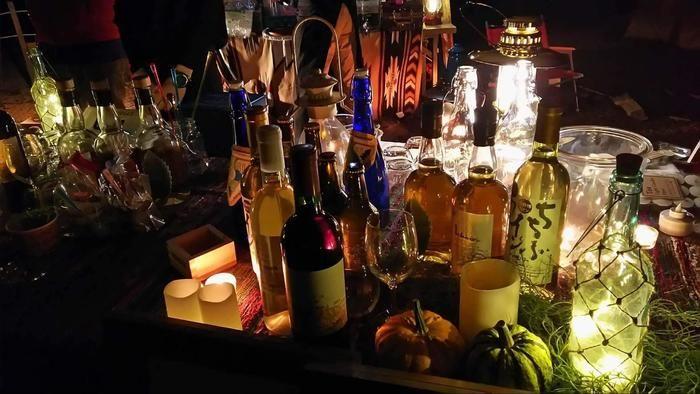 机の上におかれたたくさんのお酒の瓶がライトに照らされている様子