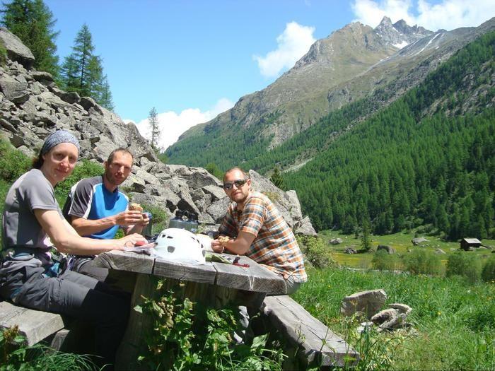 山の谷に置かれたテーブルでご飯を食べる人たち