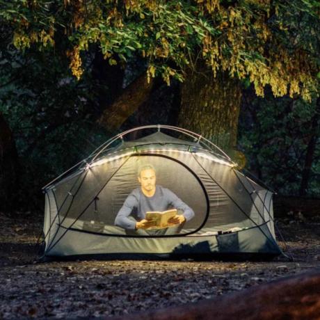 テントにロープライトを取り付けて中で本を読む男性