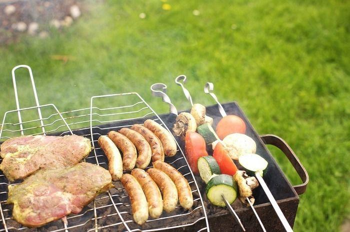 トーチバーナーで調理される肉とソーセージと野菜