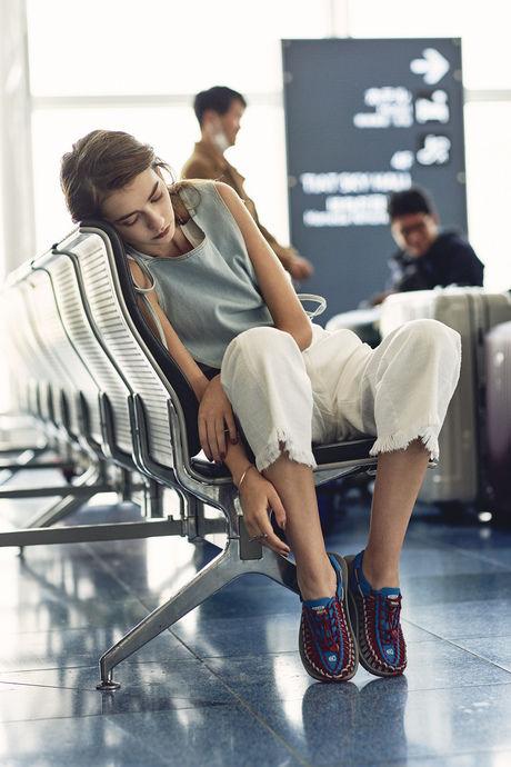 空港のいすに座っている女性