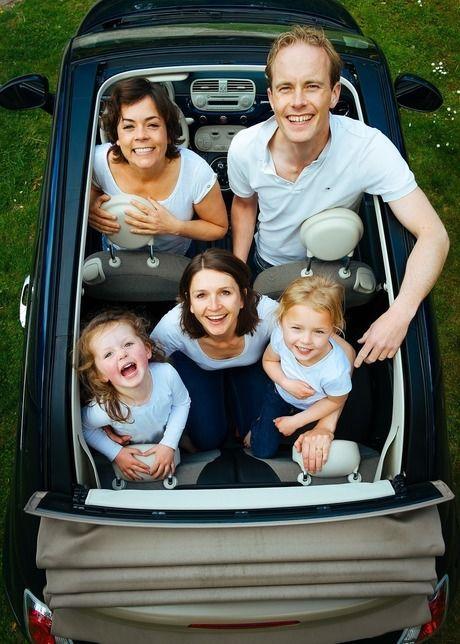 屋根を広げたオープンカーに乗る家族