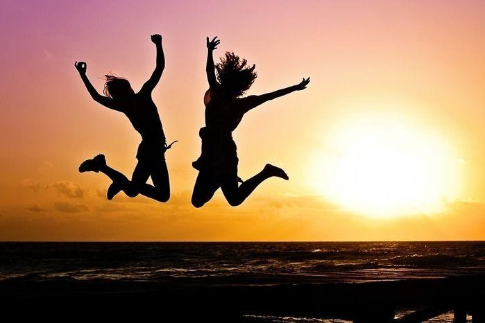 ジャンプする人と夕日の景色