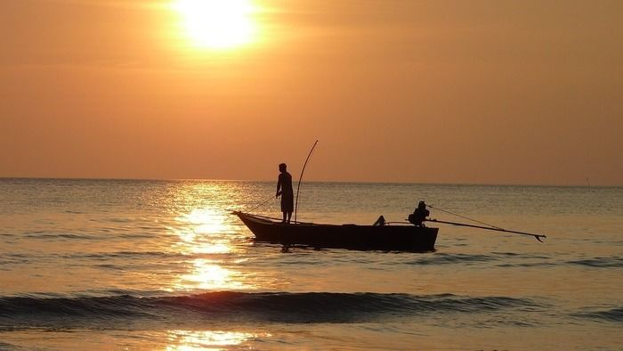 夕陽が沈む海でボートにのる2人