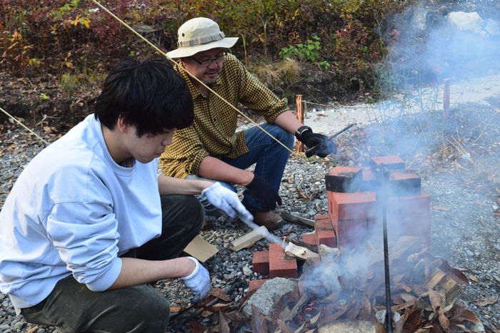 かまどに薪を焚べる人