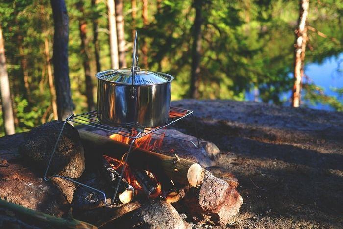 焚き火の上で火にかけられたキャンプのクッキングよ用品