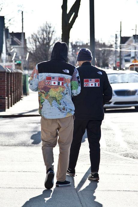 ノースフェイスとシュプリームのコラボ商品を着て歩く二人