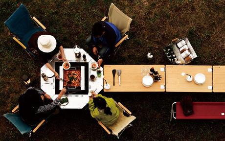 たき火用テーブルを囲む男女