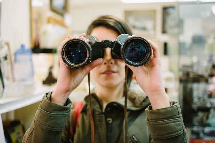 双眼鏡を持ってこちらを向いた女性