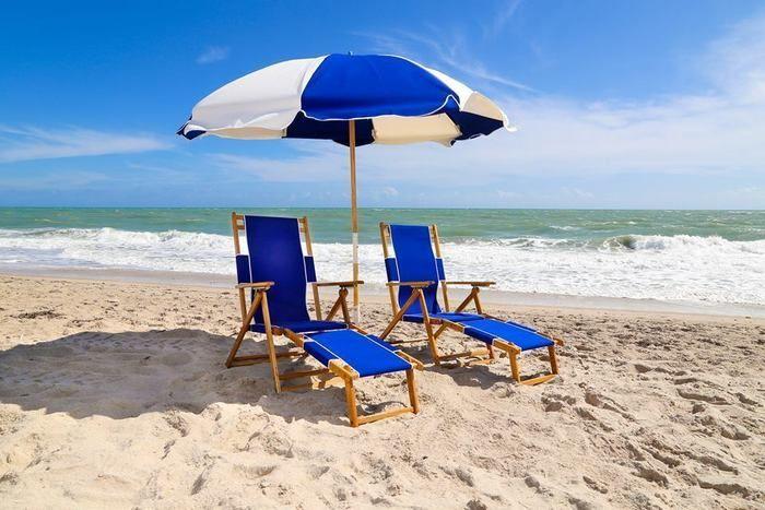 砂浜に置かれた青いパラソルとエ二ウェアチェア