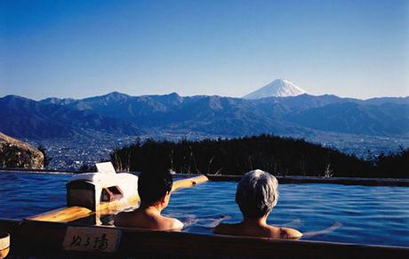 ほったらかし温泉に入る男性とそこから見える富士山の景色
