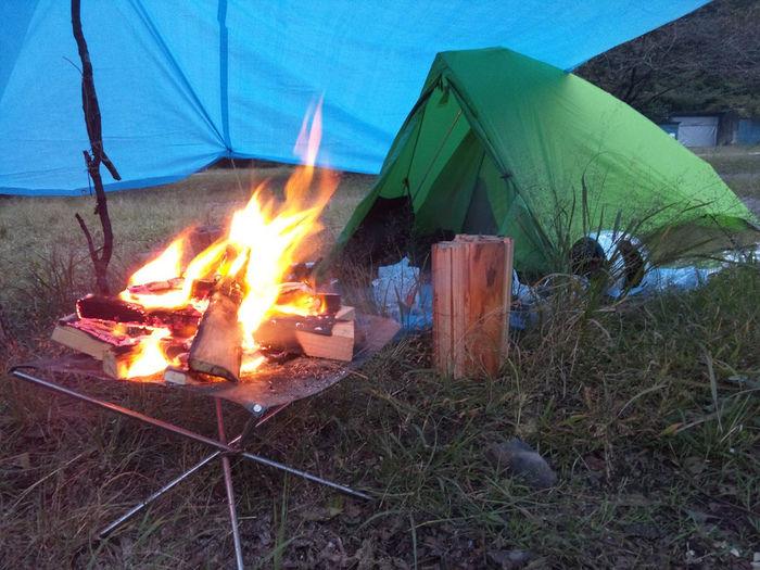 夜テントの側で焚き火をする様子