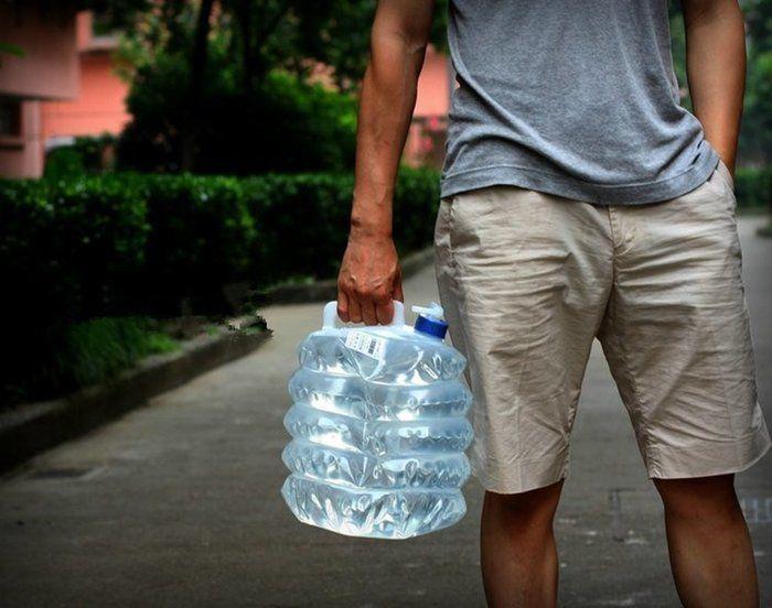 水の入ったウォータータンクを持つ男性の手元