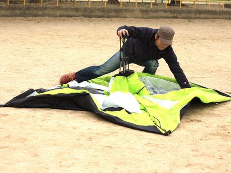 ドッペルギャンガーのワンタッチテントを組み立てる男性