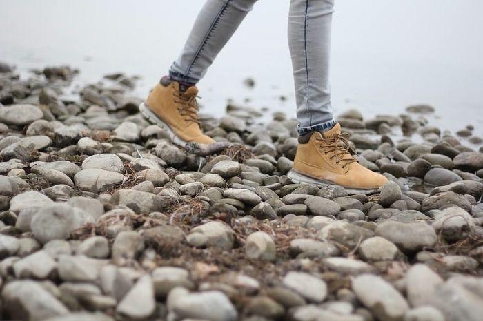 アウトドアシューズを履いて河原を歩く人の足元