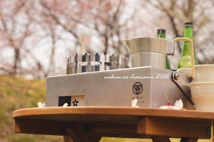 桜の下に置かれた野燗炉とお酒