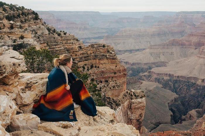 ベンドルトンのブランケットを羽織って崖に座る女性