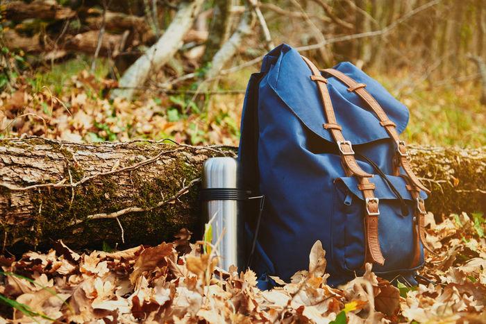 落ち葉の上に置かれたリュクと水筒