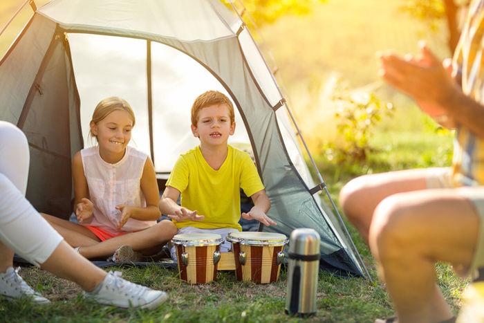 テントの前で楽器を叩いて歌を歌う子供