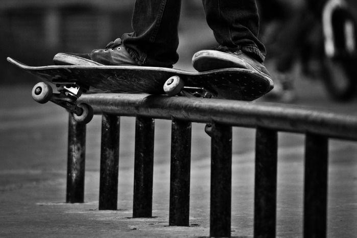 パイプの上をスケートボードで走る足元