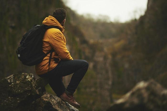 岩に座り景色を眺める男性